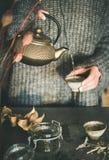 Auslaufender Tee der Frau von der goldenen Teekanne in Schale lizenzfreie stockfotos