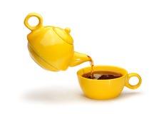 Auslaufender Tee der gelben Teekanne in eine gelbe Schale Stockbilder