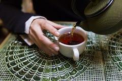 Auslaufender Tee der jungen Frau in einer Schale Lizenzfreies Stockfoto