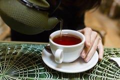 Auslaufender Tee der jungen Frau in einer Schale Lizenzfreie Stockbilder