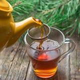 Auslaufender Tee in der weißen Schale, rustikaler hölzerner Hintergrund stockfotos