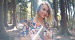 Auslaufender Tee des schönen blonden Mädchens von der Thermosflasche Lizenzfreies Stockbild