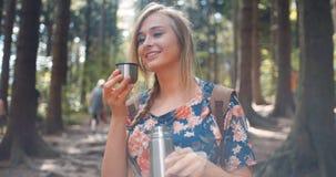 Auslaufender Tee des schönen blonden Mädchens von der Thermosflasche Stockfotografie