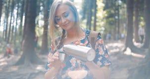 Auslaufender Tee des schönen blonden Mädchens von der Thermosflasche Lizenzfreie Stockbilder