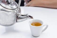 Auslaufender Tee in ein Cup Stockbild