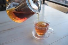 Auslaufender Tee von Teekanne zu Teetasse lizenzfreies stockfoto