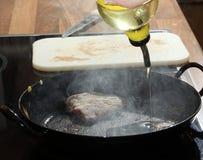 Auslaufendes Öl in heiße Wanne mit Rindfleischsteak Stockbilder