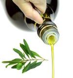Auslaufendes reines Extraolivenöl von der Glasflasche mit grünem Ölzweig stockfoto