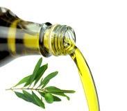 Auslaufendes reines Extraolivenöl von der Glasflasche mit grünem Ölzweig lizenzfreie stockfotos