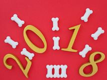 Auspicious new year 2018. An image of number 2018 in gold on bright red background with pieces of bone shape dog treats, symbolizing auspicious new year 2018 royalty free stock images