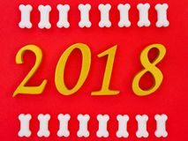 Auspicious new year 2018. An image of number 2018 in gold with white bone shape dog treats on bright red paper background, symbolizing auspicious year 2018, Year stock image