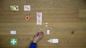 Ausrüstung der ersten Hilfe, die auf einer Holzoberfläche niedergelegt wird stock video footage