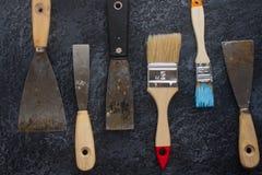 Ausrüstung rostige alte Kittmesser und -bürsten für Reparatur und dekorative Arbeiten Stockfotografie