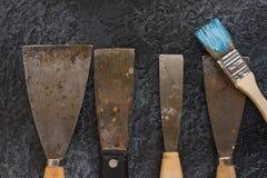 Ausrüstung rostige alte Kittmesser und -bürsten für Reparatur und dekorative Arbeiten Stockbild