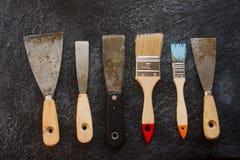 Ausrüstung rostige alte Kittmesser und -bürsten für Reparatur und dekorative Arbeiten Stockfotos