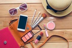 Ausrüstungsausflug des jugendlich Mädchens, Kosmetik, Zubehör, Make-up, die Schuhe, das intelligente Telefon, Tasche, Hut bereit  Stockbilder
