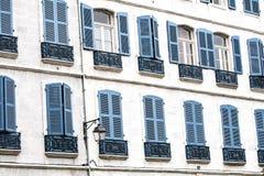 Ausrichtung von typischen Fassaden mit blauen hölzernen Vorhängen in Europa Stockbild
