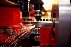 Ausschnitt des Blechs Funken fliegen von Laser durch automatischen Schnittcnc, PLC-Maschine Stockbild