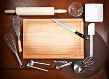 Ausschnitt-Vorstand mit anderen kochenden Hilfsmitteln Lizenzfreie Stockfotos