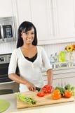 Ausschnittgemüse der jungen Frau in der Küche Stockfotos