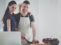 Ausschnittgemüse und -frau des jungen Mannes, die mit Laptop in der Küche stehen stockfotografie