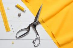 Ausschnittgewebe oder feiner Stoff mit einem Schneider scissors auf hölzernem t stockbild