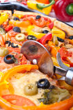 Ausschnittpizza mit einem Pizzamesser Lizenzfreies Stockfoto
