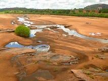 Aussicht von Fluss mit waschenden Leuten. Lizenzfreies Stockbild