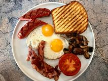 Aussie / Australian Breakfast with Brioche Toast, Fried Eggs, Crispy Bacon Sausage and Mushrooms. Traditional Food royalty free stock images