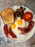 Aussie / Australian Breakfast with Brioche Toast, Fried Eggs, Crispy Bacon Sausage and Mushrooms stock photography