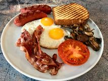 Aussie / Australian Breakfast with Brioche Toast, Fried Eggs, Crispy Bacon Sausage and Mushrooms. Traditional Food royalty free stock photography