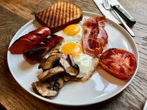 Aussie / Australian Breakfast with Brioche Toast, Fried Eggs, Crispy Bacon Sausage, Salty Pancakes and Mushrooms. Organic Foods stock images
