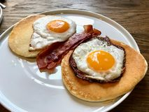 Aussie / Australian Breakfast with Brioche Toast, Fried Eggs, Crispy Bacon Sausage, Salty Pancakes and Mushrooms. Organic Foods royalty free stock photography