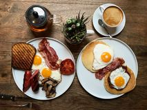 Aussie / Australian Breakfast with Brioche Toast, Fried Eggs, Crispy Bacon Sausage, Salty Pancakes and Mushrooms. Organic Foods royalty free stock photos
