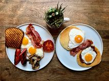 Aussie / Australian Breakfast with Brioche Toast, Fried Eggs, Crispy Bacon Sausage, Salty Pancakes and Mushrooms. Organic Foods royalty free stock image