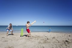 Aussie Beach Cricket. Family and friends often play versions of the sport Cricket, this family playing on the Beach stock photos