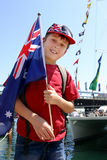 Aussie boy harbourside. Young aussie boy proudly holding flag by the harbourside mariner on Australia Day national holiday Royalty Free Stock Image