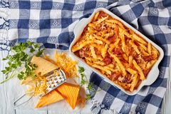 Aussie fries with bacon smothered in melted cheese. Aussie fries smothered in melted cheese and bacon in a baking dish on a white wooden table with ingredients Royalty Free Stock Images