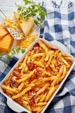 Aussie fries smothered in melted cheese, top view. Aussie fries smothered in melted cheese and bacon in a baking dish on a white wooden table with ingredients at Royalty Free Stock Image