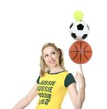 Aussie Sports. Cheerful, Aussie girl in green and gold balancing sporting balls Stock Images