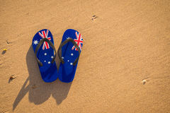 Aussie thongs on the beach at sunset. Thongs with Australian flag on the beach at sunset Royalty Free Stock Photography