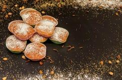 Ausstellung des kleinen Kuchens mit Tasse Kaffee, Zimt und Zucker auf schwarzer Tabelle, sehr geschmackvolle Kuchen für irgendein Stockfotografie