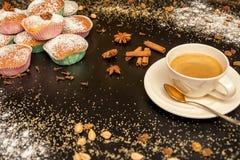 Ausstellung des kleinen Kuchens mit Tasse Kaffee, Zimt und Zucker auf schwarzer Tabelle, sehr geschmackvolle Kuchen für irgendein Stockbilder