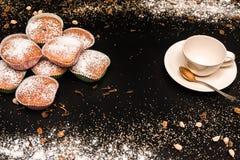 Ausstellung des kleinen Kuchens mit Tasse Kaffee, Zimt und Zucker auf schwarzer Tabelle, sehr geschmackvolle Kuchen für irgendein Lizenzfreies Stockfoto