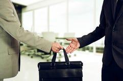 Austausch zwischen Geld und Koffer fing eigenhändig mit den Handschellen Übergabe eines Koffers tut sich zusammen stockfoto