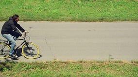 Austauschen, zum an einem Fahrrad zu arbeiten Bemannen Sie Reitfahrrad auf einem markierten Fahrradweg stock footage