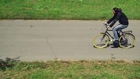 Austauschen, zum an einem Fahrrad zu arbeiten Bemannen Sie Reitfahrrad auf einem markierten Fahrradweg stock video