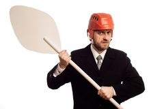 Austere businessman in a helmet and with an oar in his hands. On white background royalty free stock photo