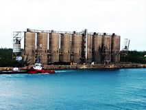 Austere , grey cement silos at FreePort harbour, Bahamas. In contrast to carefree tropical atmosphere, austere grey cement silos stand at the entrance to stock image