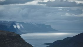 The austere Icelandic landscape with the mountains and the fjords in the background. The austere Icelandic landscape with the mountains and the fjords and the royalty free stock photo